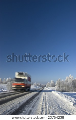 Snowy land road at winter and coming truck, deep blue sky - stock photo