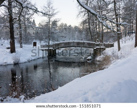 Snowy landscape with bridge and water - stock photo