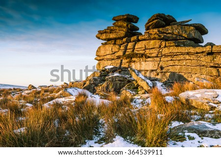 Snowy morning at rocky hills with granite tower. - stock photo