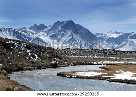 Snowy mountain and river - stock photo