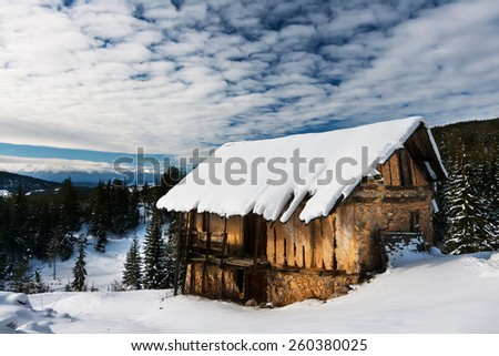 Snowy Mountain Barn and a Pine Woods Forest - stock photo