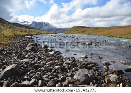 Snowy Mountain Peak and Stream  - stock photo