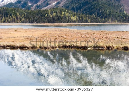 Snowy mountain reflection in water in Alaska - stock photo