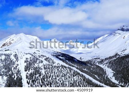 Snowy mountain ridge at Lake Louise ski resort in Canadian Rockies - stock photo