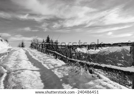 snowy mountain road in black and white - stock photo