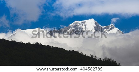 Snowy mountain with clouds.