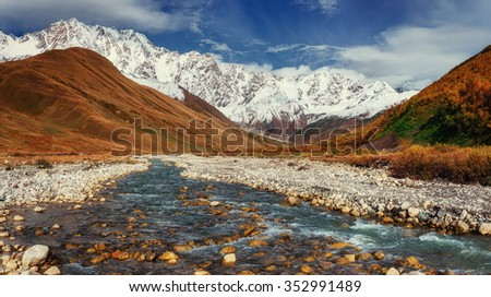 Snowy mountains and noisy mountain river. - stock photo