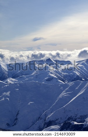 Snowy mountains and sunlight clouds at evening. Caucasus Mountains, Georgia, view from ski resort Gudauri. - stock photo