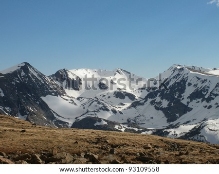 Snowy Mountains behind a Hill of Tundra - stock photo