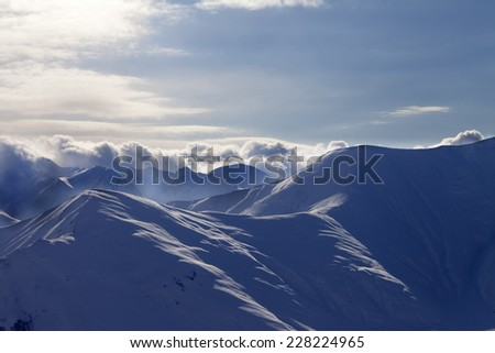 Snowy mountains in mist at sun evening. Caucasus Mountains, Georgia, view from ski resort Gudauri. - stock photo