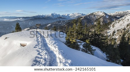 Snowy mountains on an early winter morning. Photograph was taken in Slovenia on the border with Austria. Panorama with forest, mountains, clouds and clear sky.