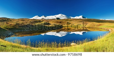 Snowy mountains reflected in lake, Plateau Ukok - stock photo