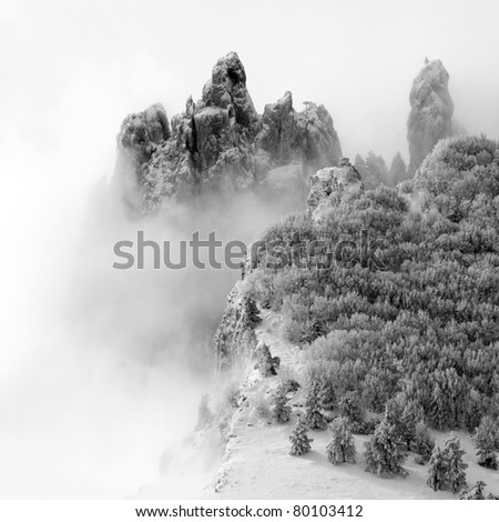 Snowy mountains with trees and fog. - stock photo