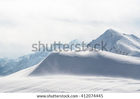 Snowy mountains with wind - stock photo