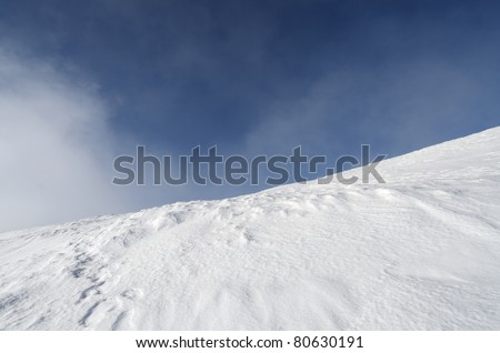snowy mountainside  in fog and blue sky - stock photo
