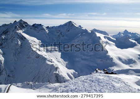 Snowy off-piste slopes at evening. Caucasus Mountains. View from ski slope of Mount Elbrus. - stock photo