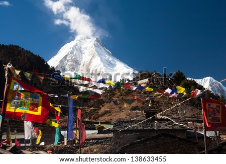 snowy peak in the clouds among the mountains of the Himalayas flags - stock photo