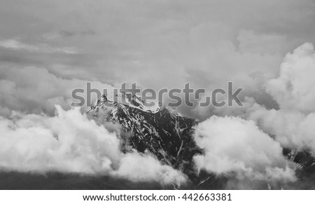 Snowy peak of the mountain shrouded in thick clouds.Black and white