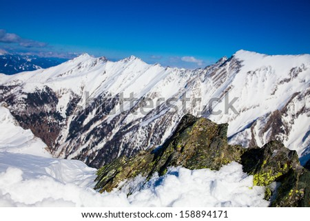snowy peaks against the blue sky, Austria; moss-covered rock in the foreground - stock photo