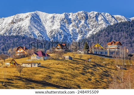 Snowy Piatra Craiului mountain ridge and scattered houses uphill in Pestera village, Brasov county, Romania. Travel destinations. - stock photo