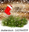Snowy pine branch with Red christmas boot on the old wooden wall - stock photo