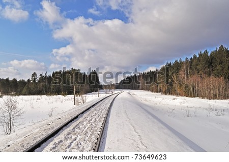 Snowy railroad in winter forest, sunny day