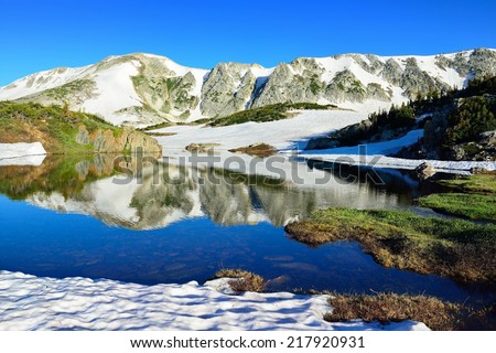 Snowy Range Mountains and alpine lake with reflection in Medicine Bow, Wyoming in summer - stock photo