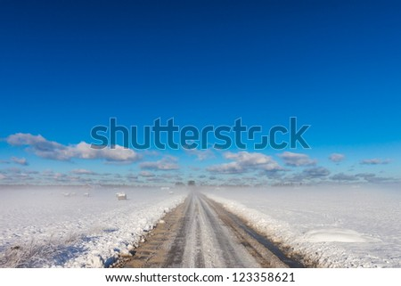 snowy road in coutryside with fogy horizon - stock photo