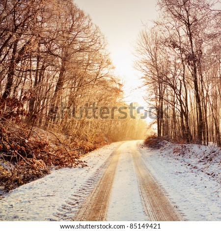 Snowy road in sunlight - stock photo
