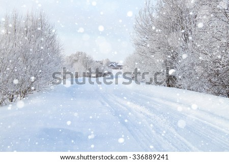 Snowy road through the forest, day. The road is covered with snow.  - stock photo