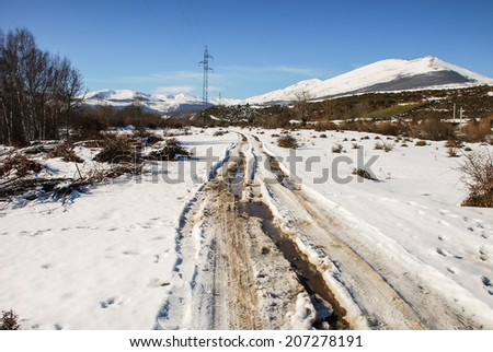 Snowy road through the valley - stock photo