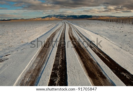 Snowy Road: Tire tracks show through light snow on a long, straight road in western New Mexico.
