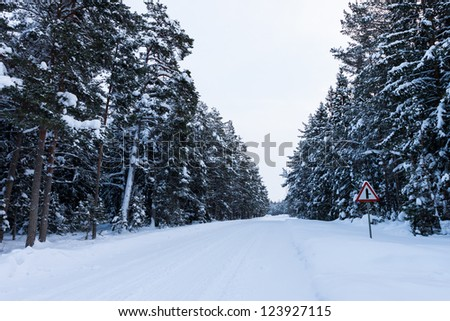 Snowy road under freezing white sky on the country side - stock photo