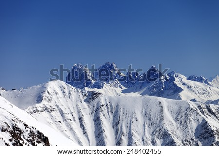 Snowy rocks at nice sun day. View from ski slope. Caucasus Mountains, Georgia. Ski resort Gudauri. - stock photo