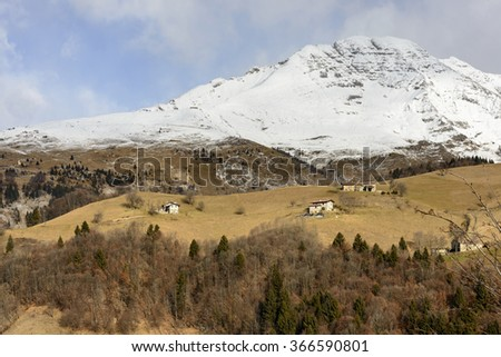 snowy rocky slopes of Arera peak border green glades with lodges, Italy  mountain lodges on green glades under the snowy rocky slope of Arera peak in Bergamo mountains in a winter with little snow - stock photo