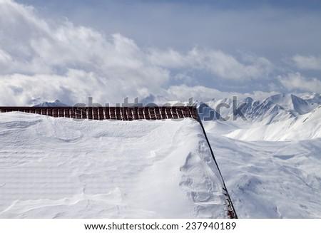 Snowy roof and cloudy mountains. Caucasus Mountains, Georgia, ski resort Gudauri. - stock photo