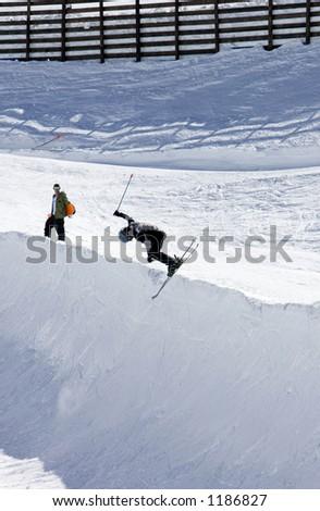 Snowy ski slopes of Pradollano ski resort in the Sierra Nevada mountains in Spain with skier in half pipe - stock photo
