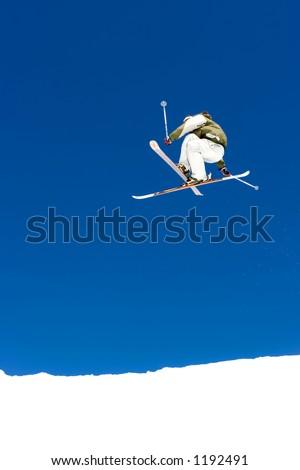 Snowy ski slopes of Pradollano ski resort in the Sierra Nevada mountains in Spain with skier making a huge jump - stock photo