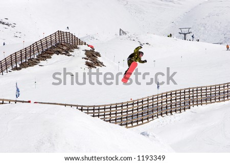 Snowy ski slopes of Pradollano ski resort in the Sierra Nevada mountains in Spain with snowboarder making a huge jump - stock photo