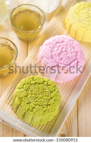 Snowy skin mooncakes.  Traditional Chinese mid autumn festival food. The Chinese words on the mooncakes is green tea with red bean paste, noble delight and lotus paste, not a logo or trademark. - stock photo