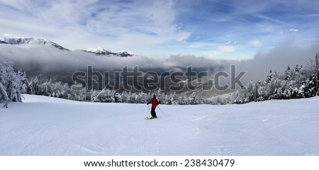Snowy slope in the mountains with single skiier - stock photo