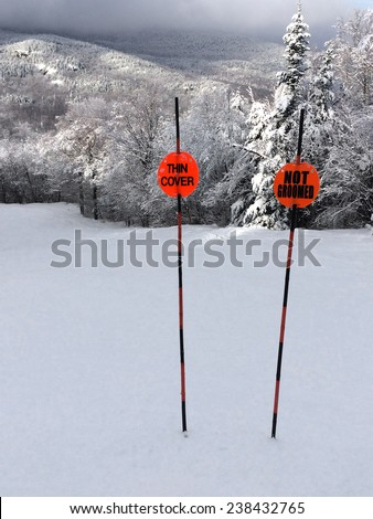 Snowy slope in the mountains with warning signs - stock photo