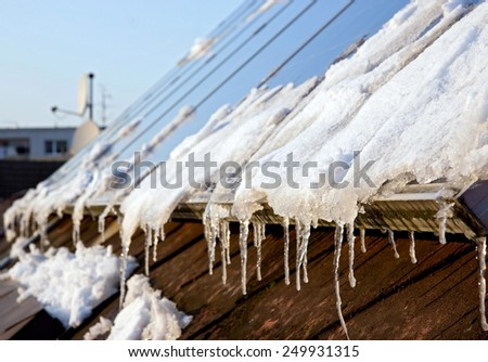 snowy solar panels on the roof of a house - stock photo