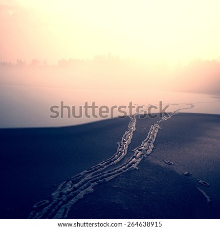 Snowy trails dressed in a blanket of snowy ice on lake. Frozen water level in the misty freeze winter evening.  - stock photo