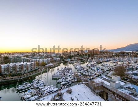 Snowy view from the Granville Bridge onto the Granville Island. Downtown skyline in Vancouver, Canada. - stock photo