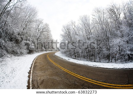 Snowy Winder Road Through Trees - stock photo