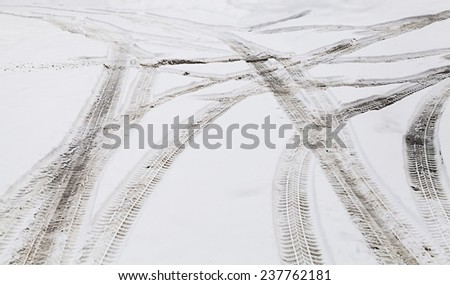 Snowy winter crossroad with tire tracks in snow  - stock photo