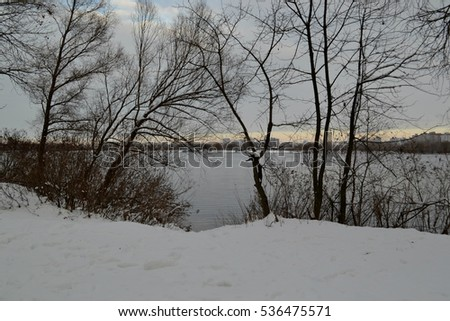Snowy winter landscape on the coast of the river