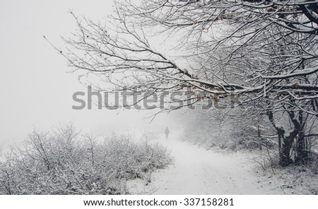 snowy winter landscape with man silhouette in the distance - stock photo