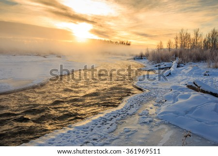 Snowy winter morning sunrise over river and forest landscape in Belgrade, Montana.